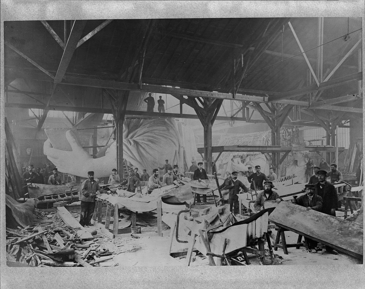 Workmen constructing the Statue of Liberty in Bartholdi's Parisian warehouse workshop; first model; left hand; and quarter-size head-, ca. 1882.