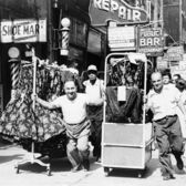 Men pulling racks of clothing on busy sidewalk in Garment District, New York City