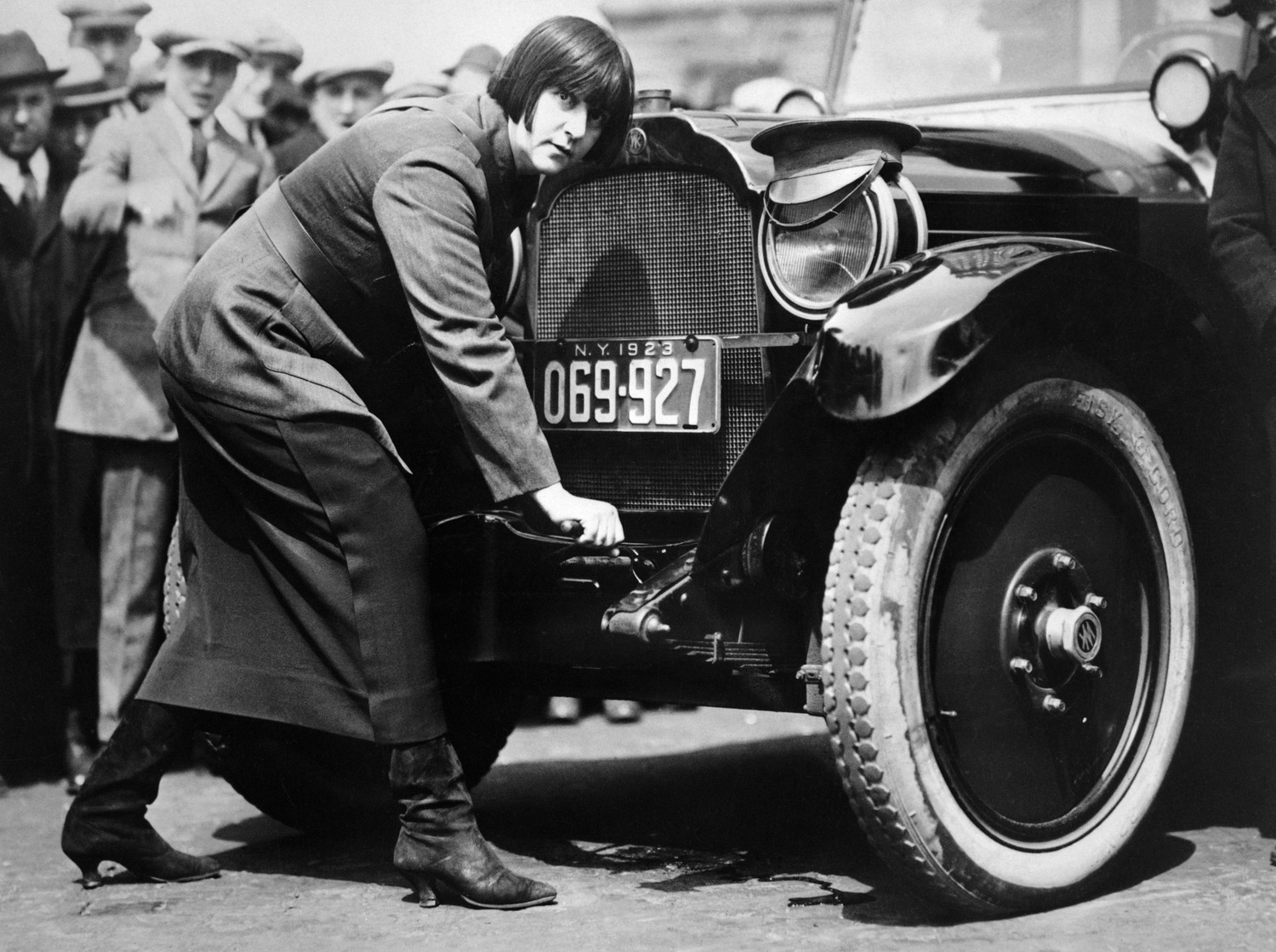 Miss Maude Odell, one of the first women taxi drivers in New York. She is cranking car (Hub Taxicab Corporation), 1923.