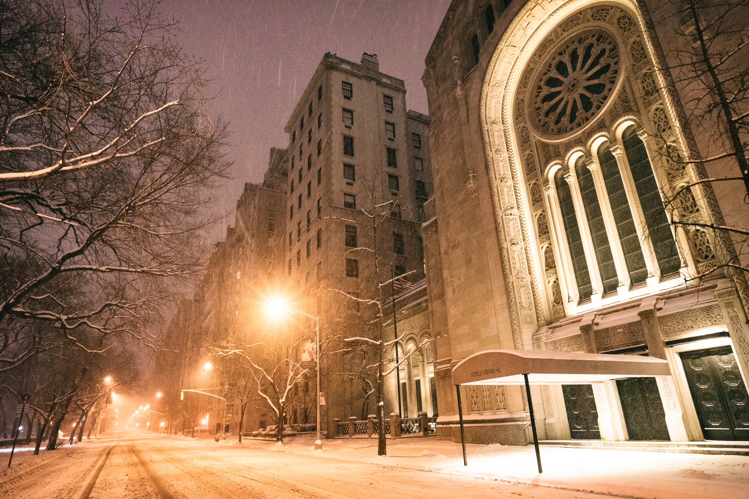 "New York City - Snow - Winter Storm Juno - Empty 5th Avenue - Temple Emanu-el | Juno: The first snowstorm of 2015 in New York City.  ---  (Note: My <a href=""http://www.amazon.com/gp/product/1440339589/ref=as_li_tl?ie=UTF8&camp=1789&creative=9325&creativeASIN=1440339589&linkCode=as2&tag=nyththle0e-20&linkId=ER6GYT5FRYNMEPLF"" rel=""nofollow"">New York photography book</a> released worldwide in stores/online recently and has photos similar to this  [full info below])  ---  I have been photographing New York City during snowstorms at night for the past 5 years. When it comes to experiencing <a href=""http://nythroughthelens.com/tagged/snow"" rel=""nofollow"">New York City in the snow</a>, I relish the challenge. The more gusty, snowy, and brutal the storm, the more of a chance that I will be out in it traipsing around New York City with my cameras in tow.  When I heard that the MTA was suspending all transit service (and most vehicles) at 11 pm, I made the decision to take the train up to the Upper East Side prior to 11 pm to deposit myself up there with the intention of walking from the Upper East Side to Times Square and then walking the several miles back to the Lower East Side (whew!!).  The streets were eerily empty.  Emptier than they are usually at night during snowfall. Since there was a ban on all vehicles aside from snow plows and emergency services, there were practically no cars at all on the streets. Even taxis were banned from the streets!  I walked in the middle of avenues and streets that are usually teeming with cars.  There was an eerie sense of calm.  It was magical.   ---  This is part of a post that I posted to my NYC photography blog. If you are curious enough to look at the photos there, here is the link to the post:  <a href=""http://nythroughthelens.com/post/109291619025/new-york-city-snow-winter-storm-juno-i"" rel=""nofollow"">New York City - Winter Storm Juno</a>   ----  * As mentioned above - My New York City coffee table book that released in stores/online worldwide recently.   Tons of information about my <a href=""http://www.amazon.com/gp/product/1440339589/ref=as_li_tl?ie=UTF8&camp=1789&creative=9325&creativeASIN=1440339589&linkCode=as2&tag=nyththle0e-20&linkId=ER6GYT5FRYNMEPLF"" rel=""nofollow"">New York photography book</a> with sample pages (including where to order and what stores are carrying it) here:  <a href=""http://nythroughthelens.com/post/92873566010/ny-through-the-lens-the-book-i-am-super"" rel=""nofollow"">NY Through The Lens: A New York Coffee Table Book</a> ---   View my New York City photography at my website <a href=""http://nythroughthelens.com/"" rel=""nofollow"">NY Through The Lens</a>.  View my Travel photography at my travel blog: <a href=""http://travelinglens.me/"" rel=""nofollow"">Traveling Lens</a>.  Interested in my work and have questions about PR and media? Check out my:  <a href=""http://nythroughthelens.com/about"" rel=""nofollow"">About Page</a> 