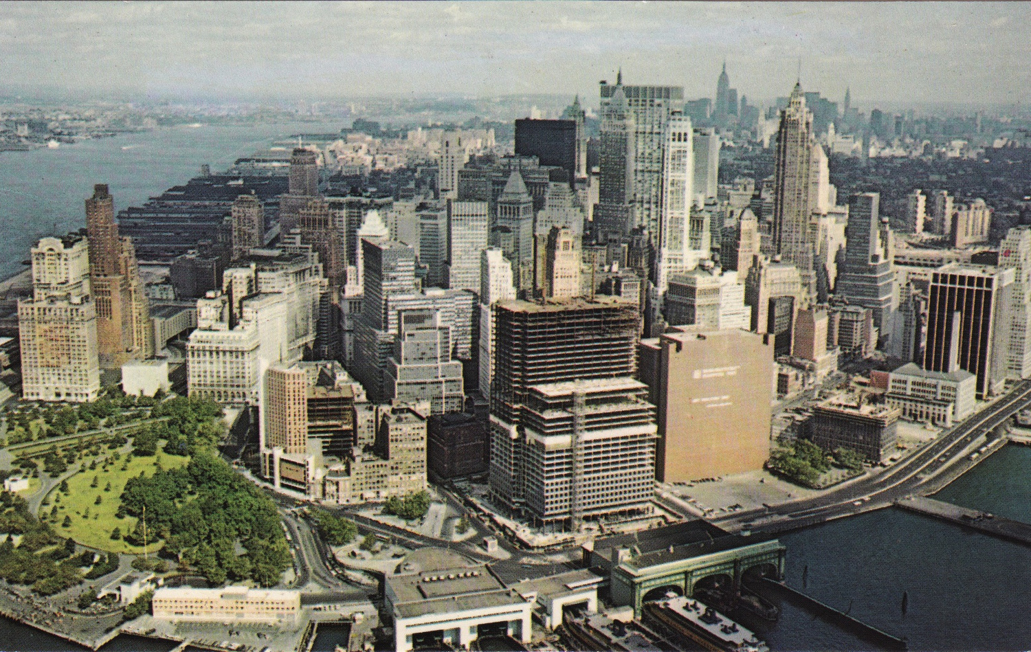 Looking northwest, change has begun as several boxy buildings are under construction near South Street and the FDR Drive as seen directly behind the Staten Island Ferry terminal (1965).