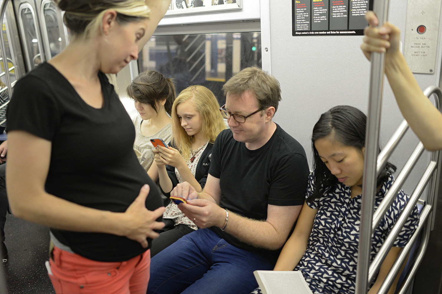 "Pregnant Woman Stands on Subway While People Sit and Play with Phones | You can use this photo for non-commercial purposes if you give credit, under this <a href=""https://creativecommons.org/licenses/by-nc/3.0/us/"" rel=""nofollow"">Creative Commons license</a>. For-profit media organizations also may use this, but as editorial content only (as illustrations for stories, for example, but not as advertising). Credit must read: Richard Yeh / WNYC  We'd love to know if you're using this photo - send us an email (jkeefe@wnyc.org)!"