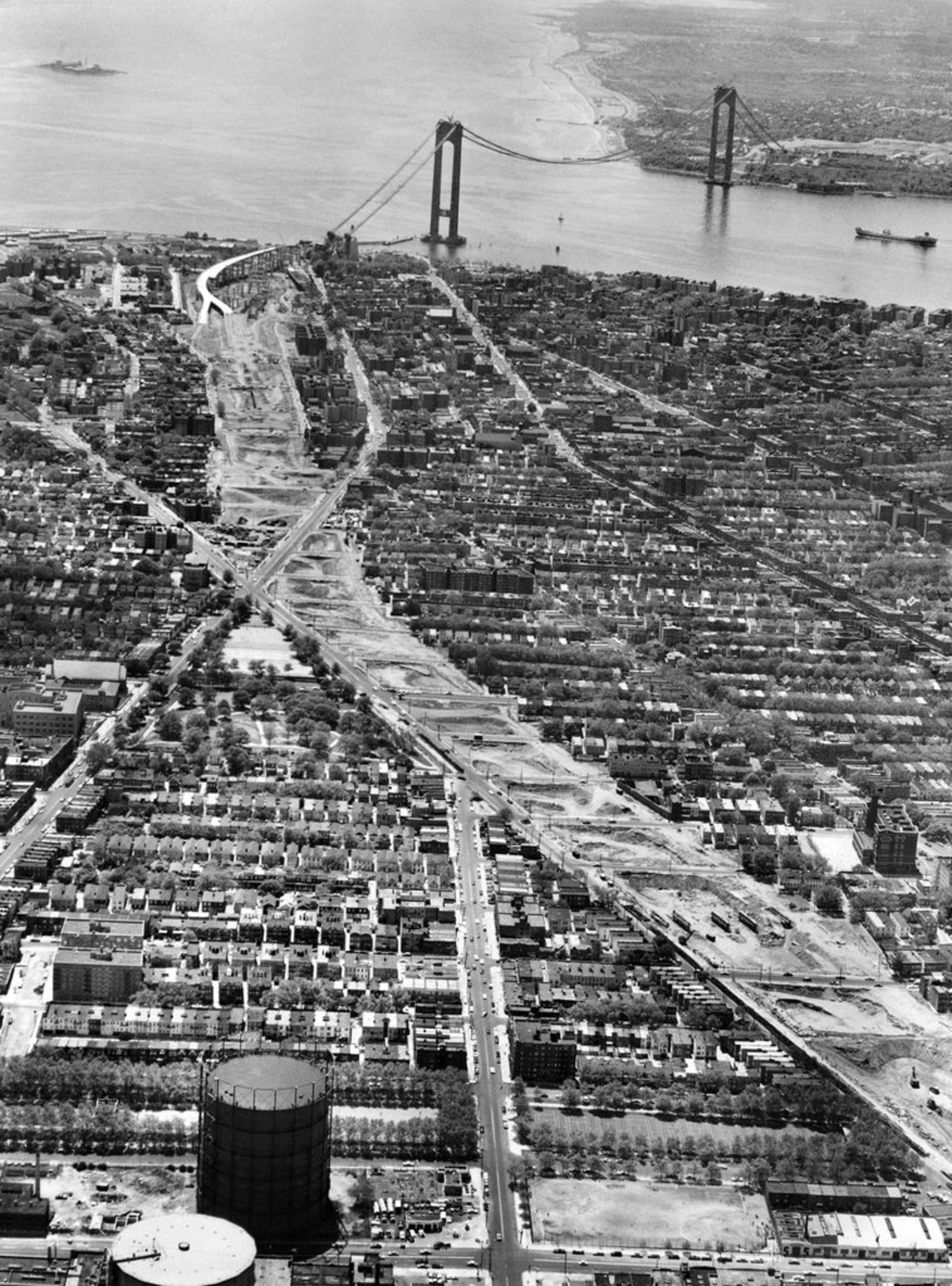 "May 17, 1963: A view of sleepy Staten Island and ""The Bridge — the $325,000,000 Verrazano-Narrows span, which will join Fort Wadsworth on the island with Fort Hamilton in Brooklyn when it is completed."" The booming growth of the island chagrined some, who ""gloomily forecast intolerable overcrowding of schools, stores, living space and roads. They are less sanguine than the enthusiasts about the solution of such problems as lack of sewers, of final mapping and paving of streets and of 'City Hall red tape' that discourages prospective industrial development."""