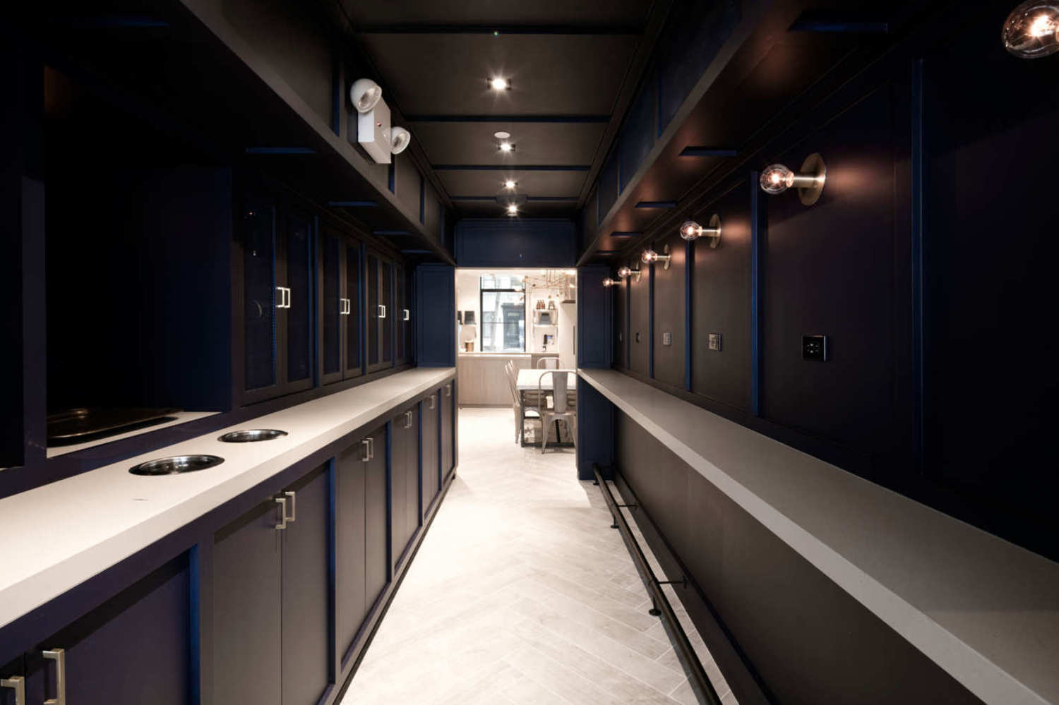 The connecting passageway is equipped with standing ledges and wall outlets — the only ones in the entire space.