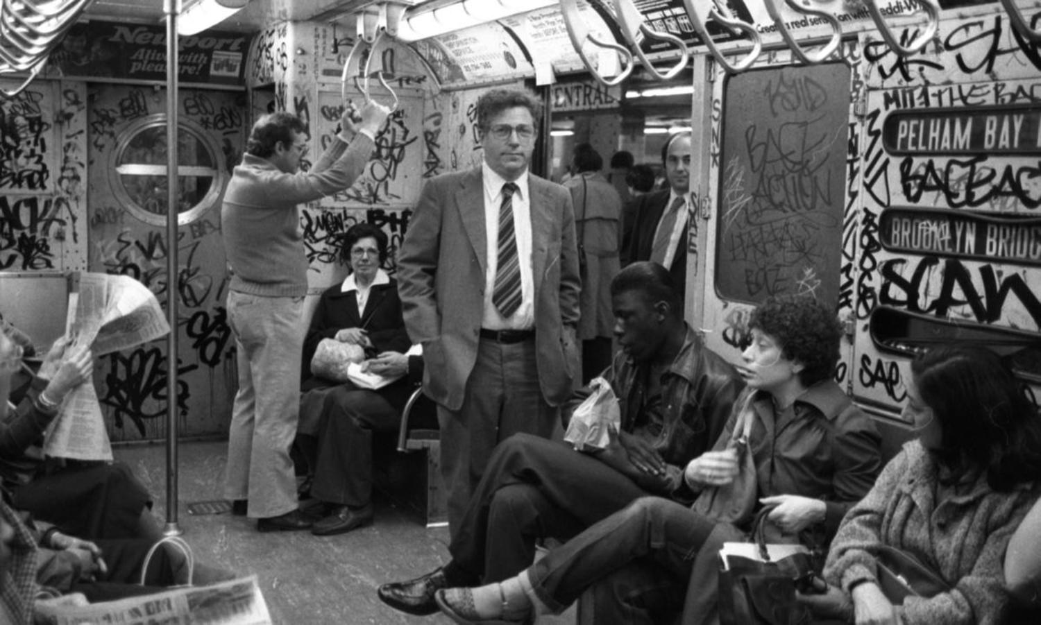 1980's: A man wearing a crisp business suit pops against this subway car scrawled over with heavy graffiti.