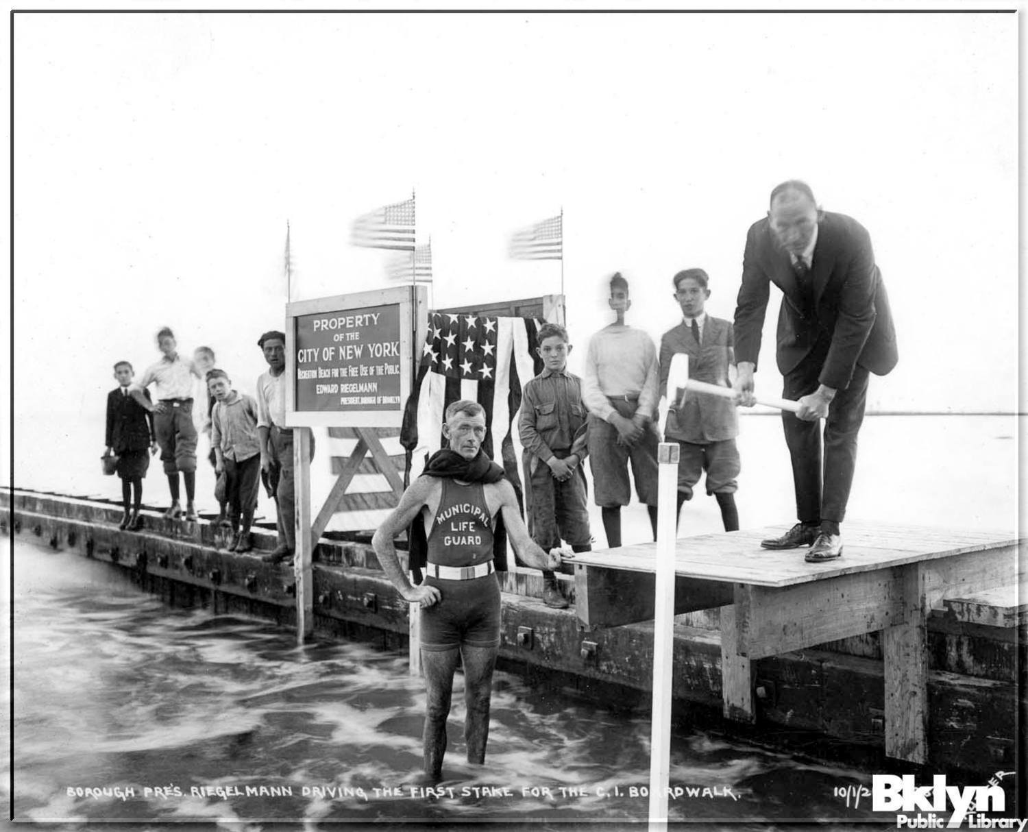 Brooklyn borough president Riegelmann driving the first stake for the Coney Island boardwalk, October 1st, 1921