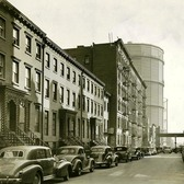 East 20th Street facing east towards 1st Avenue in 1938 with two huge gas holders in the distance.