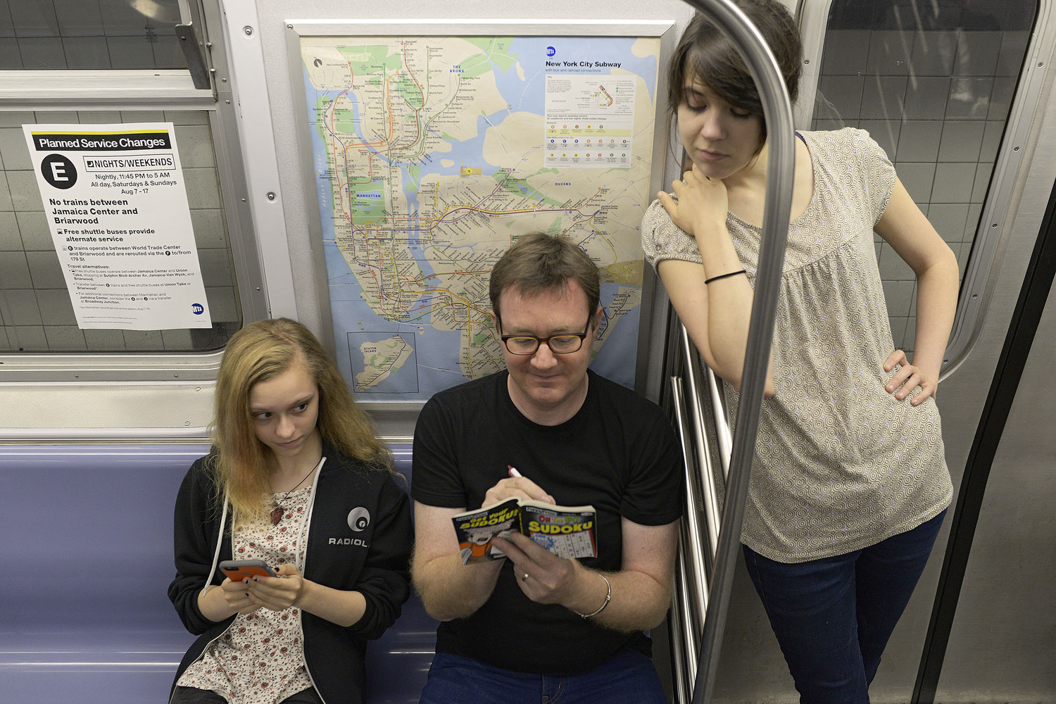 "Man Playing Sudoku on Subway While Women Look Over His Shoulder | You can use this photo for non-commercial purposes if you give credit, under this <a href=""https://creativecommons.org/licenses/by-nc/3.0/us/"" rel=""nofollow"">Creative Commons license</a>. For-profit media organizations also may use this, but as editorial content only (as illustrations for stories, for example, but not as advertising). Credit must read: Richard Yeh / WNYC  We'd love to know if you're using this photo - send us an email (jkeefe@wnyc.org)!"