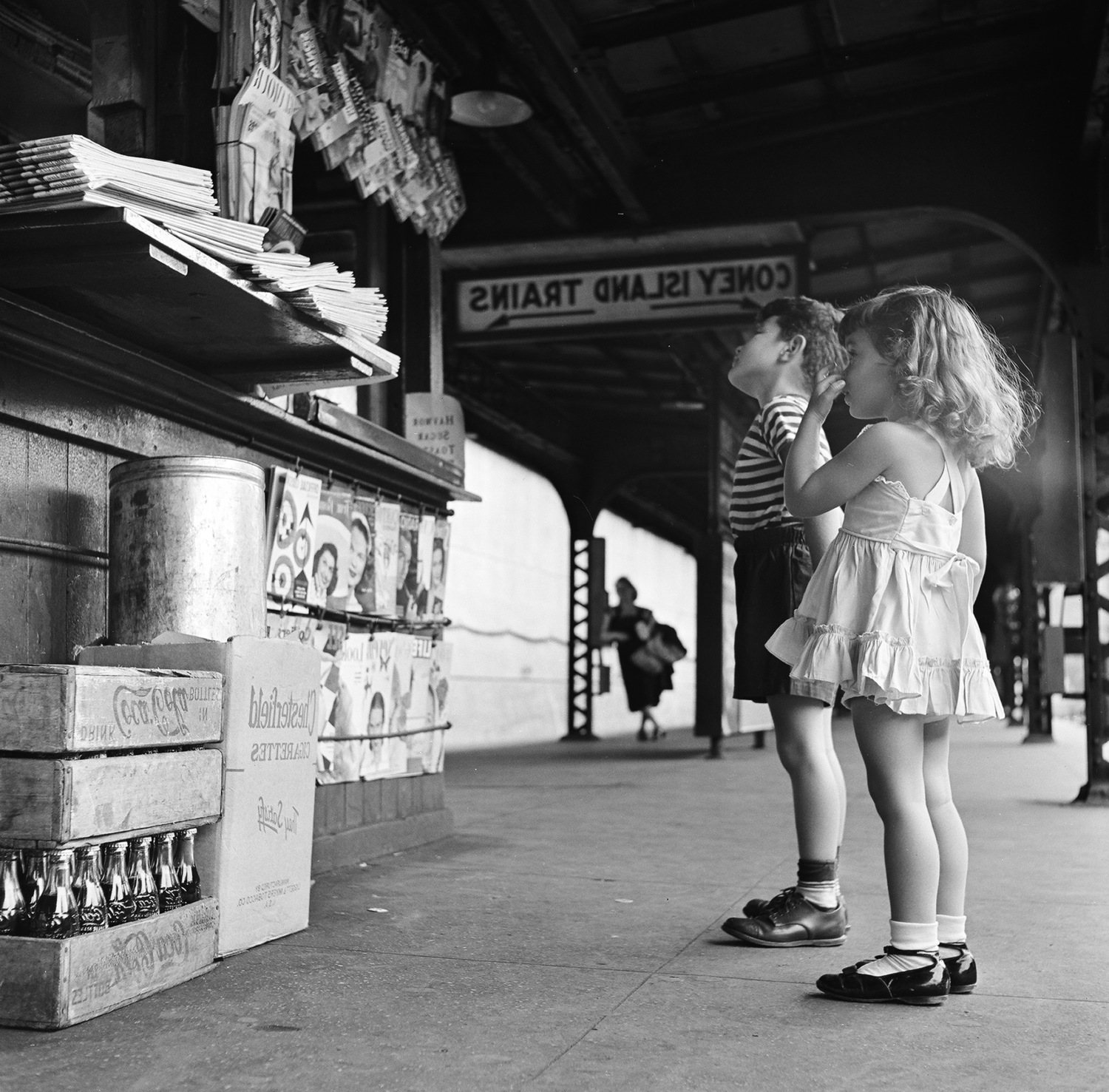A brother and his sister look up at a newsstand, located on the platform of the New York city subway, as they wait for the train to Coney Island, New York, 1948.