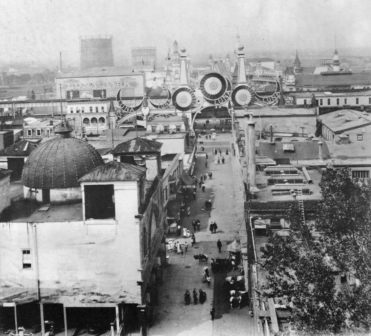 Luna Park on a busy weekend looking north along Jones Walk from entrance on Surf Ave. Women in dresses and men in suits with straw hats. Large industrial gas tanks loom in the distance. Coney Island. Brooklyn, New York.  1925