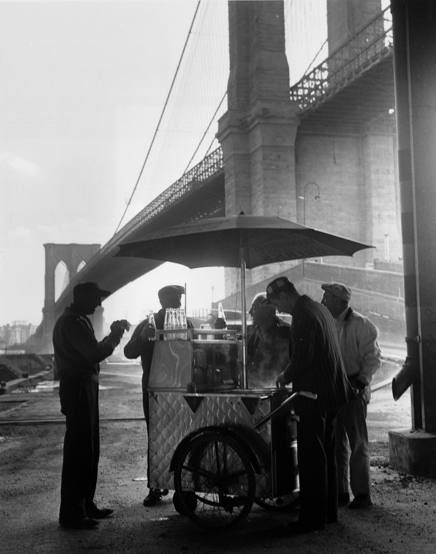 A group of workers getting refreshments from a portable snack stand underneath Brooklyn Bridge.