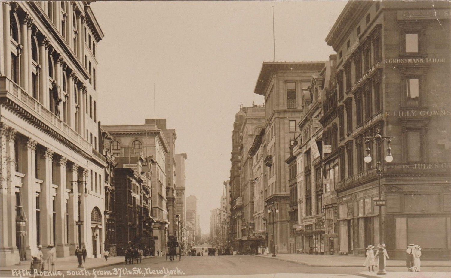 "From around 1903, Fifth Avenue is lightly trafficked looking south from 37th Street. In this remarkably clear photo postcard, in the lower left corner we see a ""white wing"" one of New York's sanitation workers, who appears to be chatting with a well dressed lady. Across on the west side of the street four young women are walking north having just passed Jules K. Weiss & Co. whose tailoring establishment can be seen on a sign directly behind the street lamp. All the visible vehicular traffic is horse drawn."