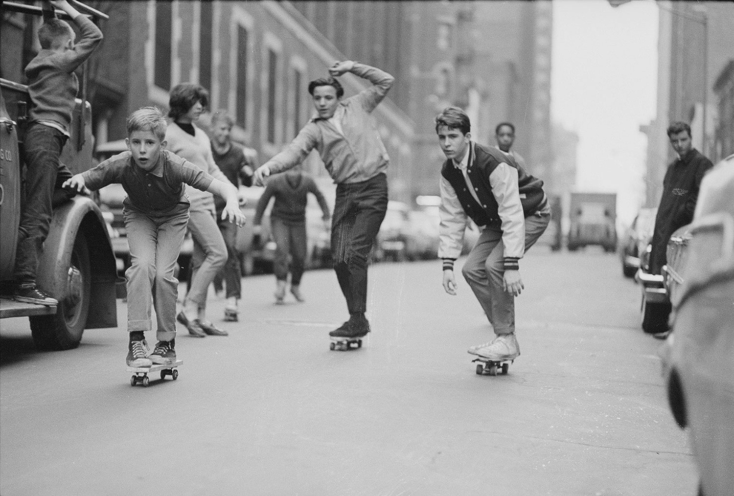A group of boys skate down a street that probably hasn't been paved since.