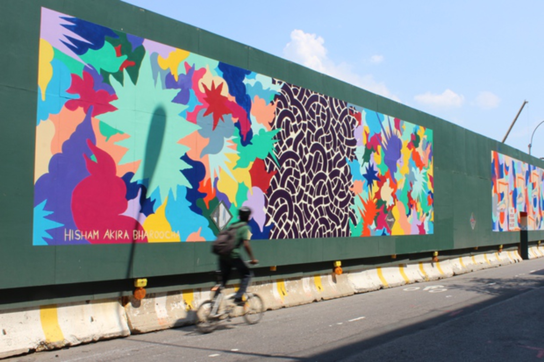 A biker rides by a mural by artist Hisham Akira Bharoocha on Dean Street.