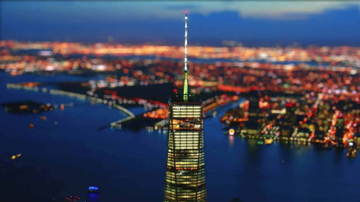 One World Trade Center's soaring spire is the focus of the colourful image above as the lights of Jersey City illuminate the background.