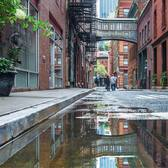 Strolling under the historic Staple Street skybridge after the rain. This skybridge was constructed in 1907 and was used to transport patients from the horse-drawn ambulances to the hospital facilities across the street. TriBeCa, Manhattan, New York City