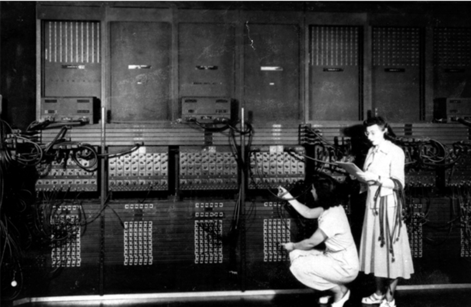 Two women wiring the right side of the ENIAC with a new program, ca. 1946. Courtesy US Army. Standing: Marlyn Wescoff, Crouching: Ruth Lichterman.