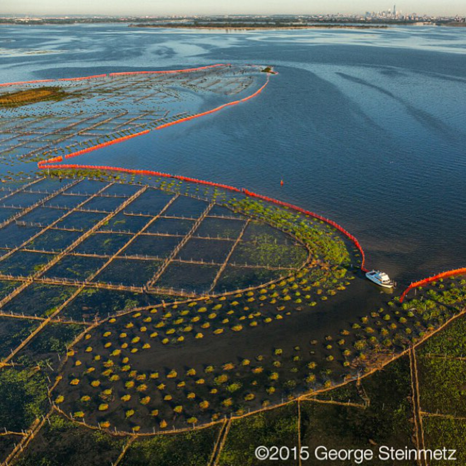 Photograph by George Steinmetz @geosteinmetz / @thephotosociety  It may look by a new work the artist Christo, but this Hurricane Sandy restoration project in Jamaica Bay was supervised by the Army Corps of Engineers. The orange barrier diminishes wave erosion to help marsh plants get established and serve as a haven for fish and wildlife. Hard to believe this is #NewYorkCity, but if you look carefully #OneWorldTrade is visible in upper right.