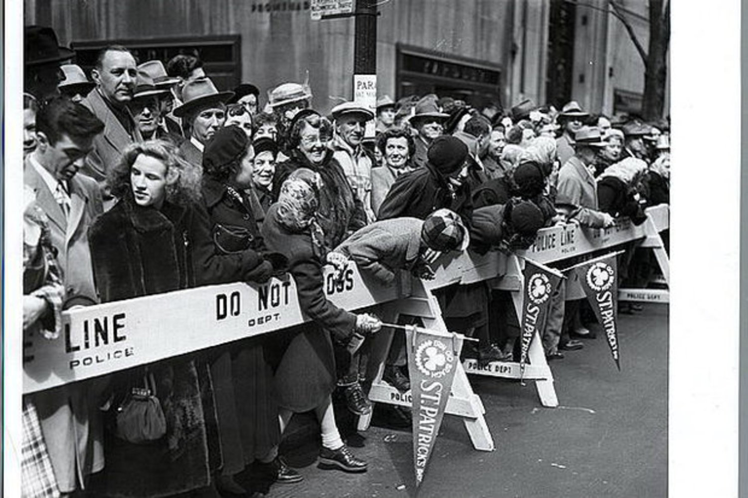 A crowd waits by along the St. Patrick's Day Parade route on 5th Avenue in 1951 New York.