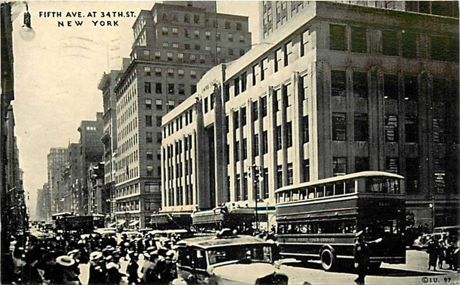 In just 20 years Fifth Avenue has changed dramatically. Looking south on Fifth Avenue from 34th Street in 1935, the Waldorf-Astoria is gone and the Empire State Building is in its place. The Empire State is directly behind the double deck Fifth Avenue bus. Pedestrian and vehicular traffic is substantial and in front of the bus a policeman deals with the congestion.