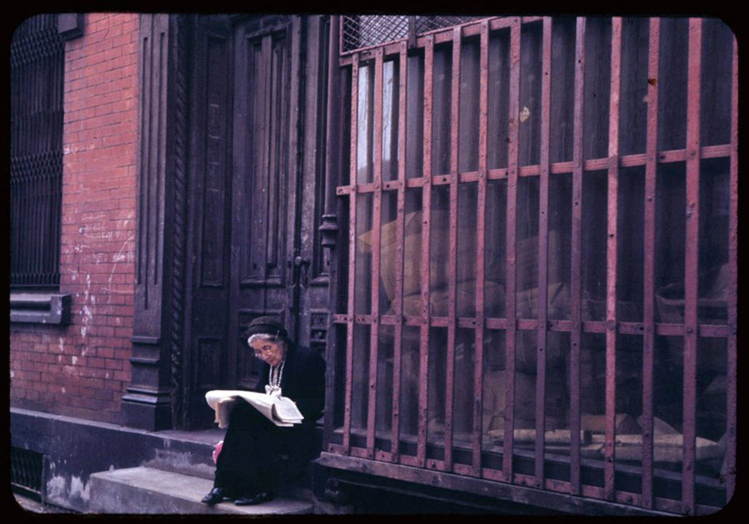 This woman enjoys her Sunday newspaper on a stoop in the Lower East Side.