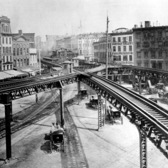 This is an 1878 view of the Third Avenue Line El train tracks, looking north up the east side of the Bowery, at Chatham Square in lower Manhattan, New York.