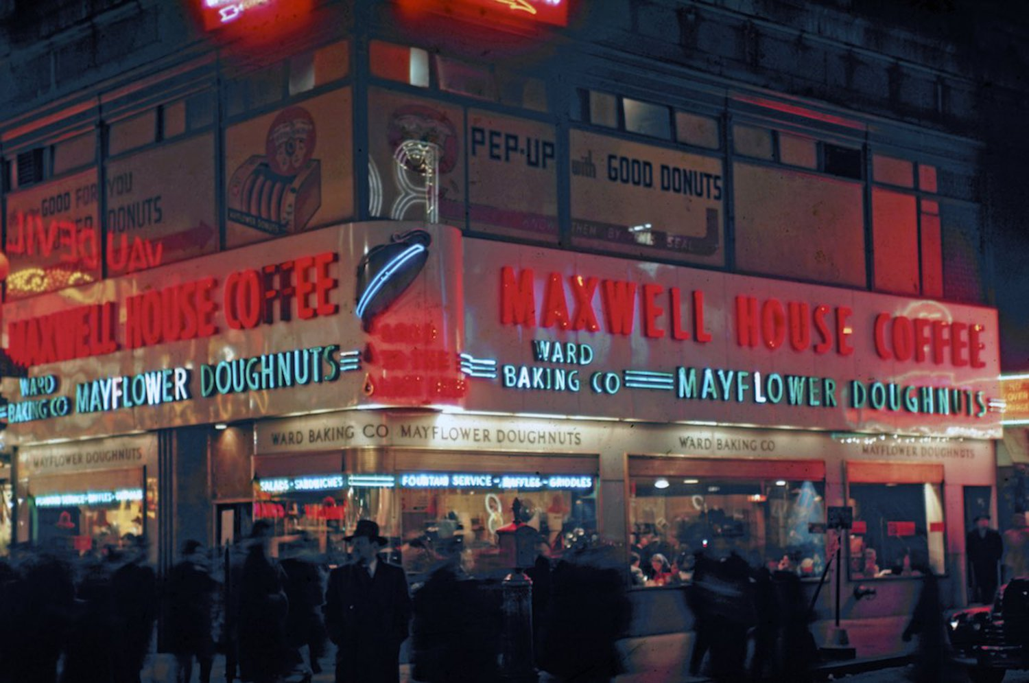 1946 The neon-illuminated Maxwell House and Mayflower Doughnuts coffee shop at the north-west corner of the busy intersection of West 42th Street (which runs left to right) and Broadway.