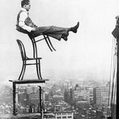 A daredevil balances on the back legs of a chair atop other furniture, 20 stories up in New York, circa 1920.