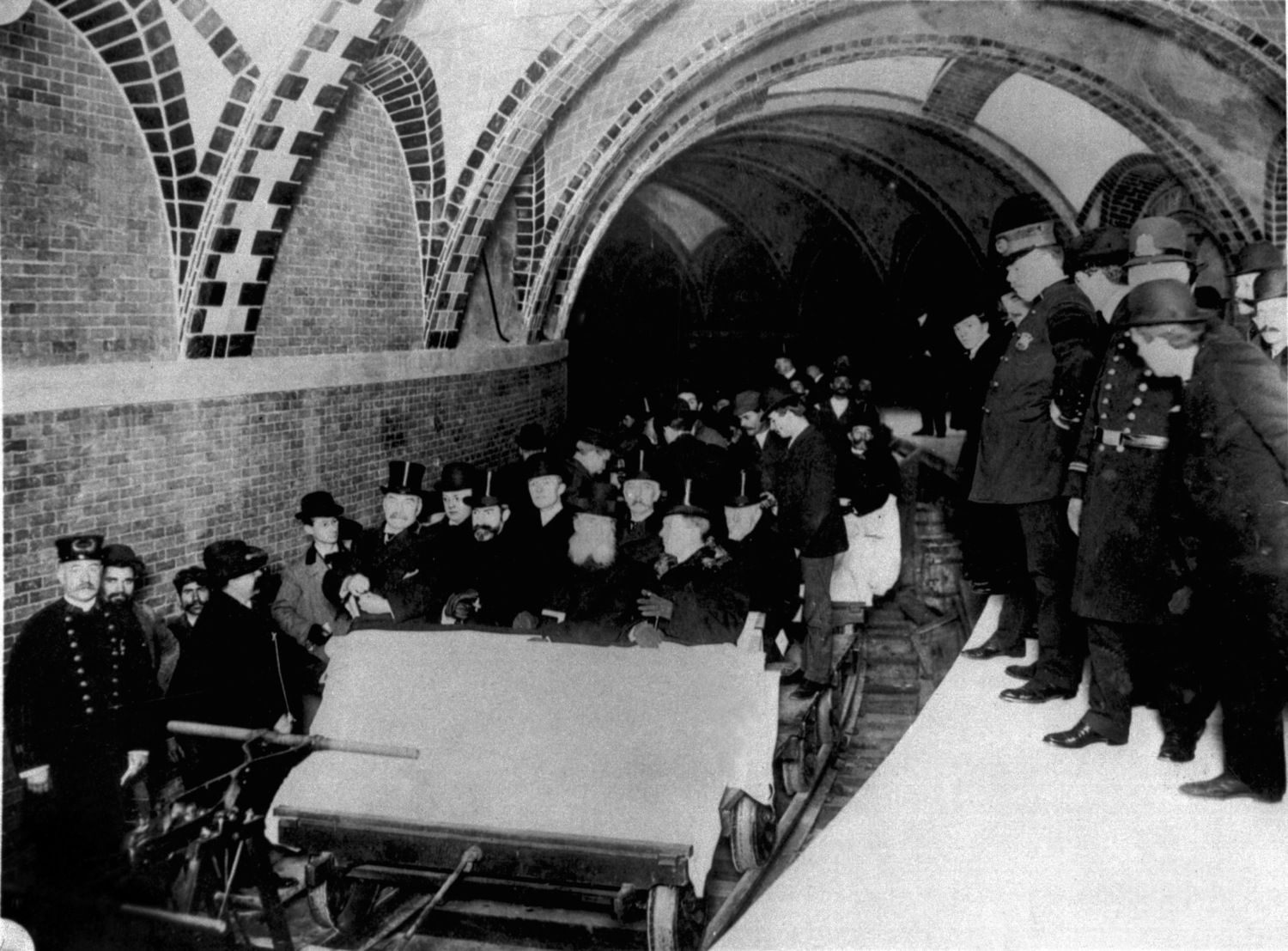 This group of financiers and city officials get a tour of New York City's first subway in January 1904 while the city's policemen stood by on the platform at City Hall Station. Seated toward the front of the ceremonial flat car are Alexander Orr, August Belmont, John B. McDonald, and Mayor George B. McClellen.