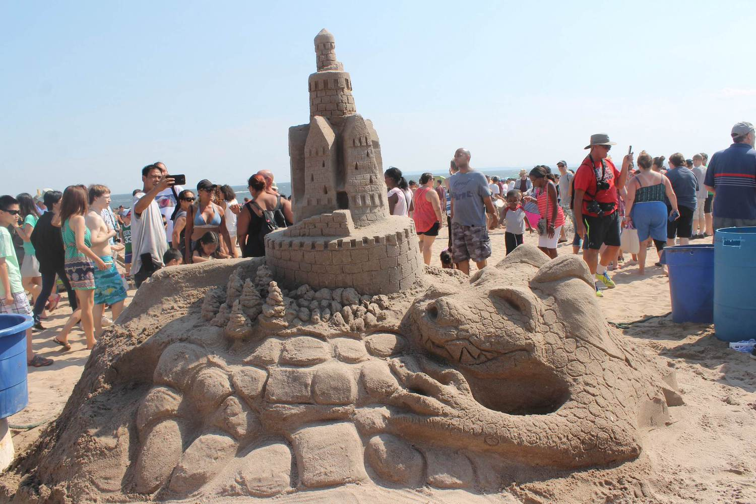 A fearsome dragon appears to be protecting (Or ready to swallow) this sand castle.