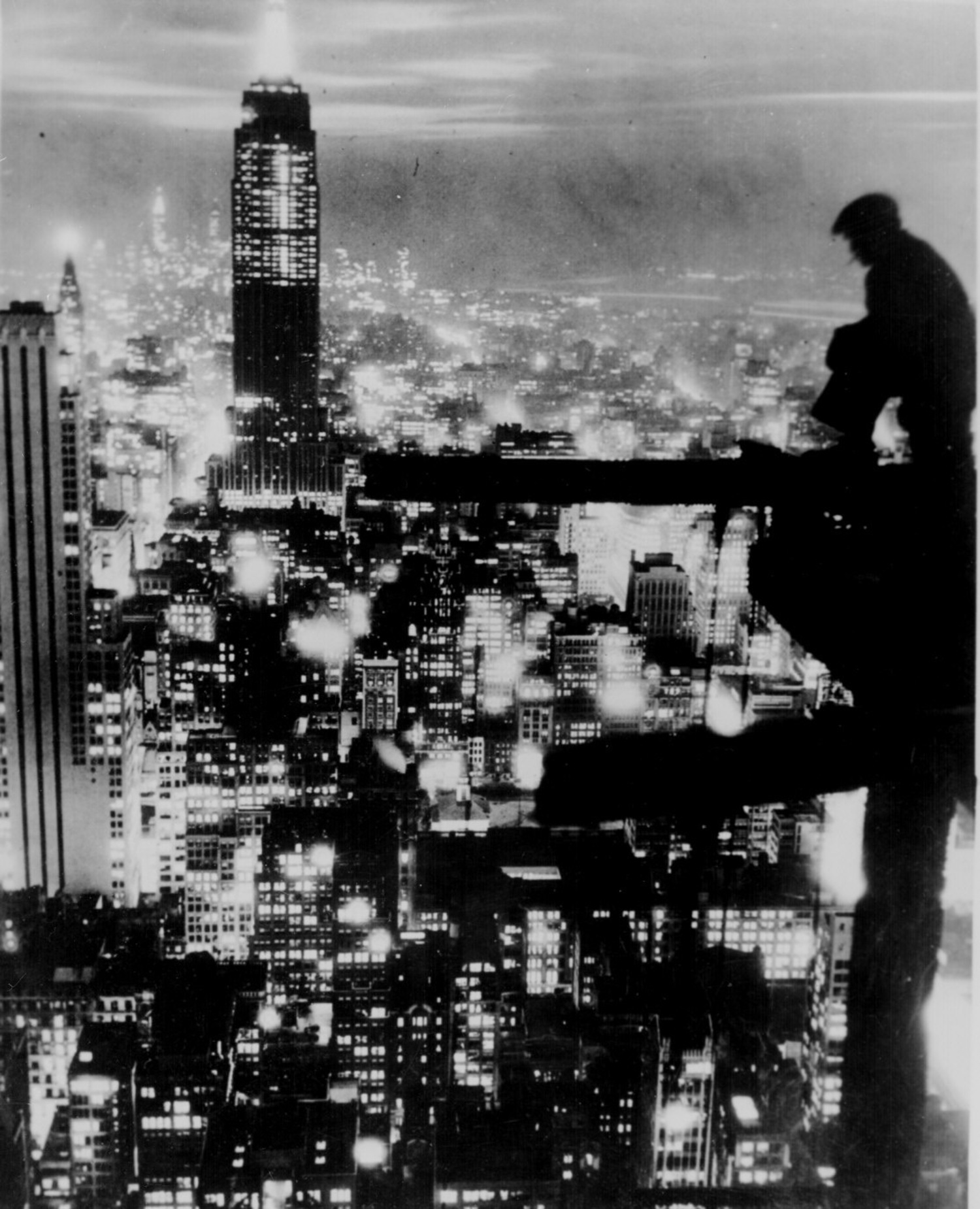 A man sits on a girder above New York City at night, ca. 1935