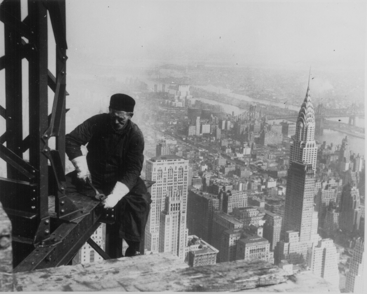 Workman, perched on the end of a beam, bolting together the framework of the Empire State Building, New York City, 1930. Photograph by Lewis Hine