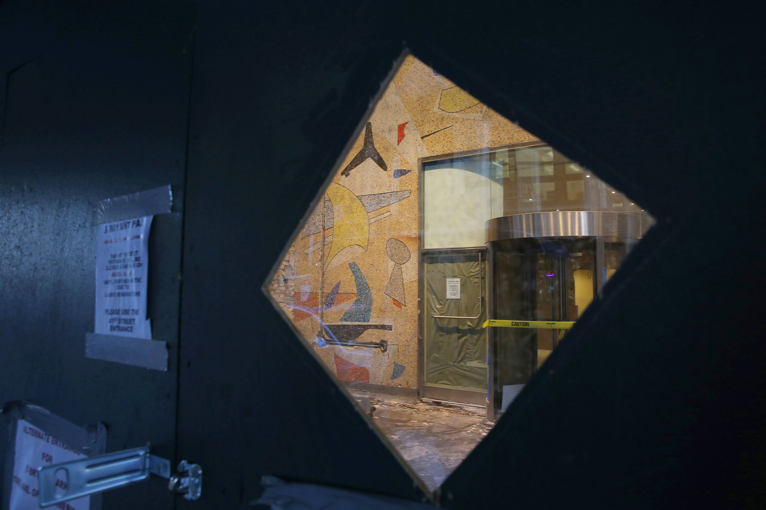 The mural seen through a clear panel in a construction wall.