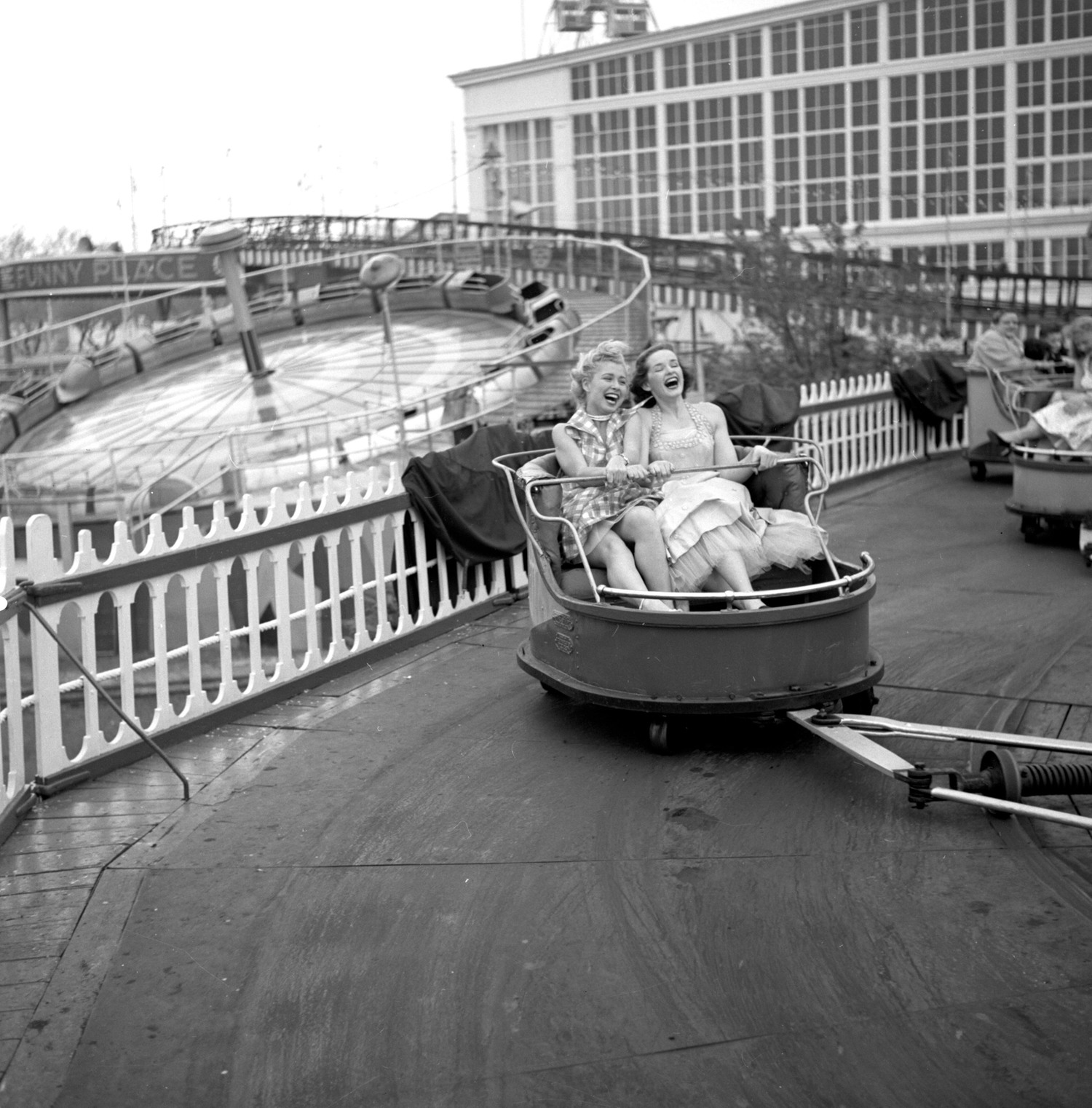 "Models from the CBS gameshow, ""The Big Payoff,"" Cindy Robbins and Pat Conway ride The Whip designed and built by W.F. Mangels Company of Coney Island, at Steeplechase Park. Coney Island, Brooklyn, NY."