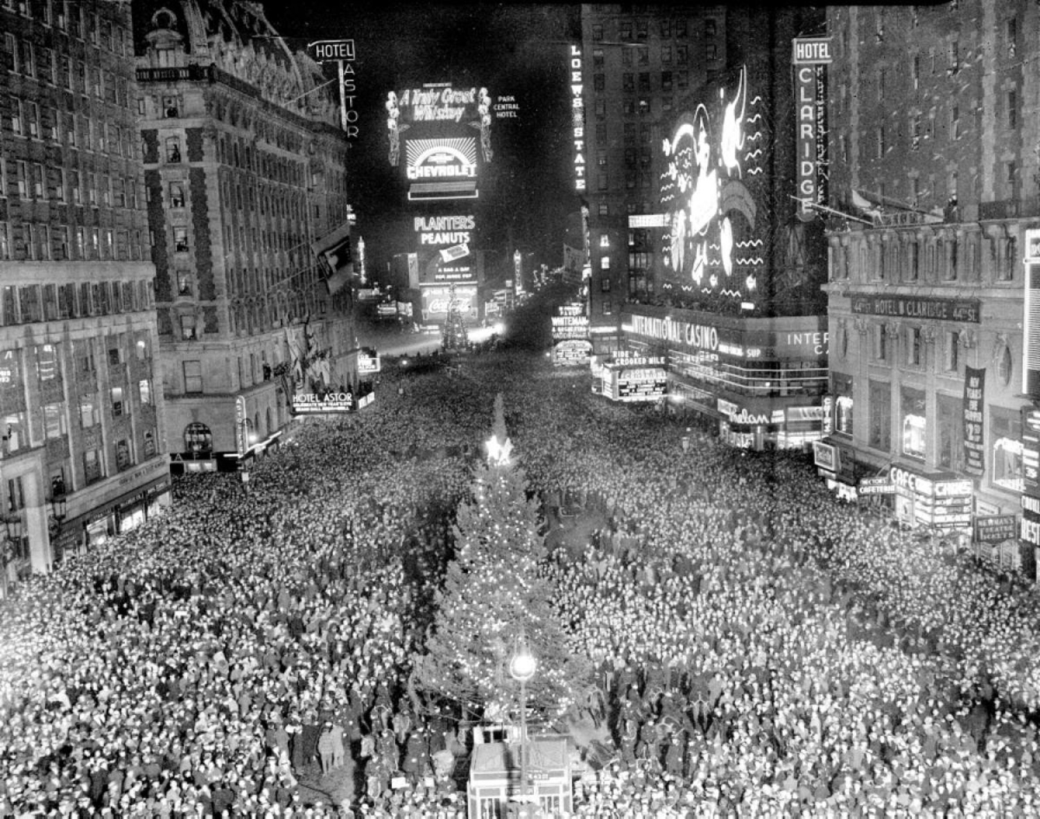 Looking north from 43rd street, a huge crowd gathers around a Christmas tree to welcome in 1938.