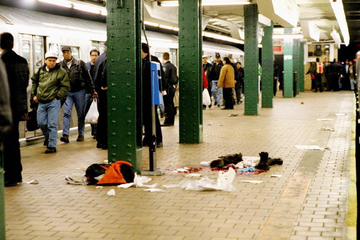 1990's: Subway riders walk by a horrific crime scene on the platform of the 125 St. station after an unidentified person was shot, leaving behind a pool of blood and clothing of the victim.