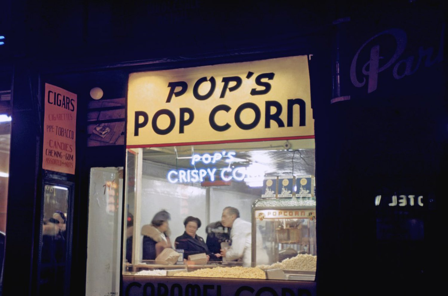 1946 Pop corn vendor in Times Square at night with patrons inside.