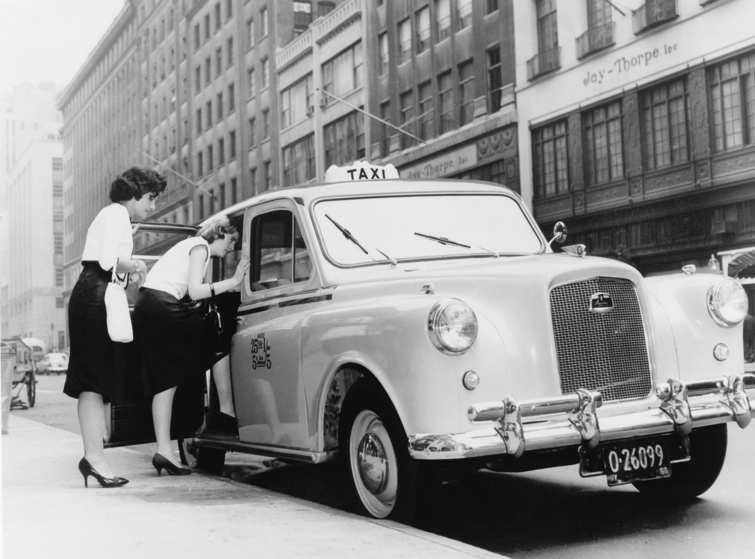 Two women getting into the first British-built Austin taxi licensed in New York, 1960.