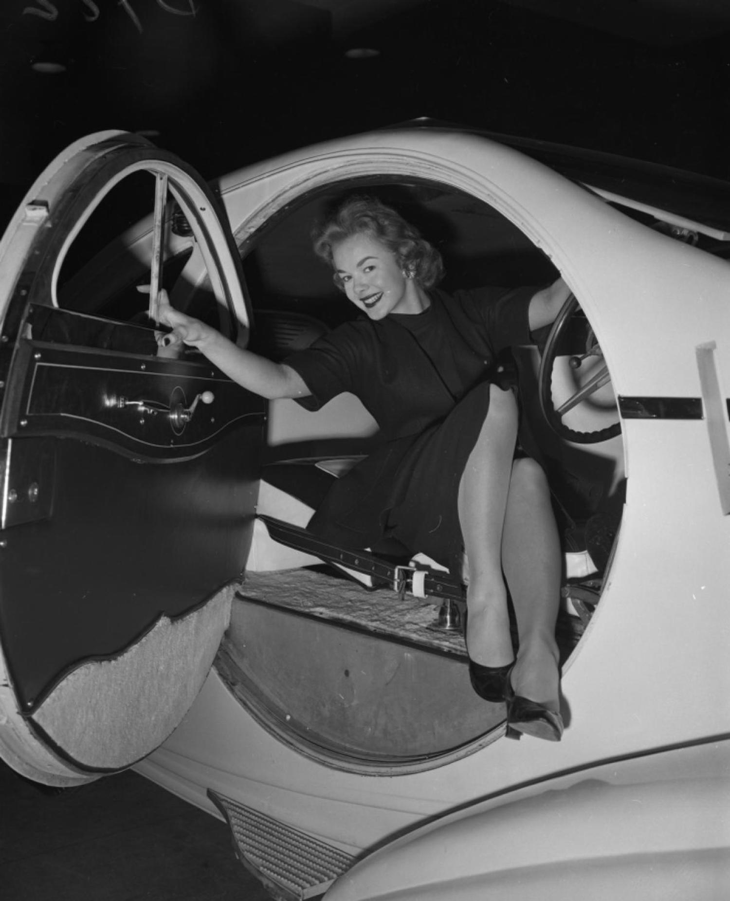 """Notice those lines? It's really a dream. Every man should have one. It's the $100,000 Rolls-Royce sports car. Oh, the girl? She's model Marjorie Holler,"" read the original Daily News caption for this photo from the Motor Sports Show."