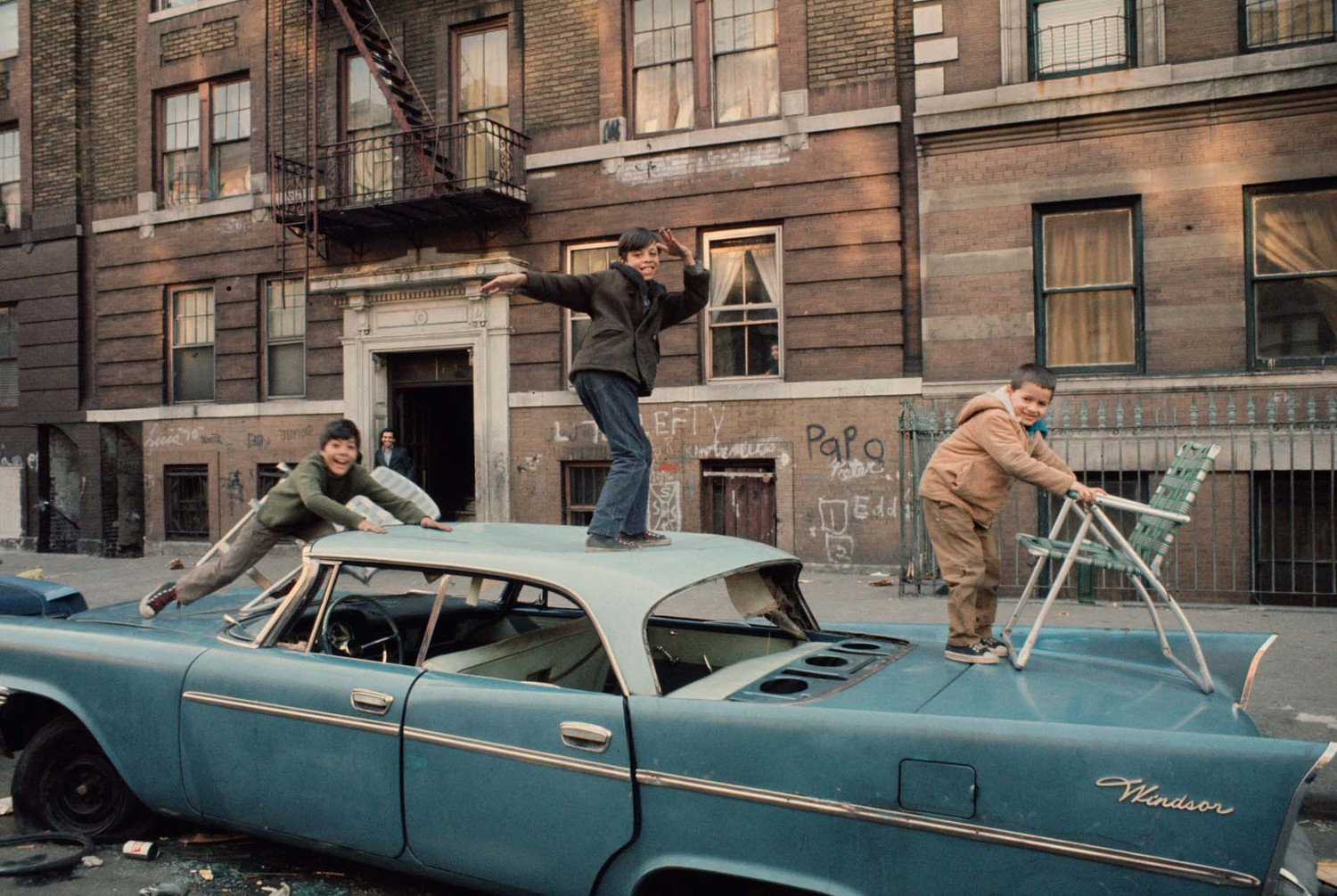 Kids playing on an abandoned car in South Bronx, 1970