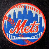 METS..... | Are a team based in the New York City borough of Queens. They play in Major League Baseball's National League East Division. This was a patch on a person's sweat jacket that I saw while waiting on a checkout line at the Shop Rite supermarket in Carmel, New York.