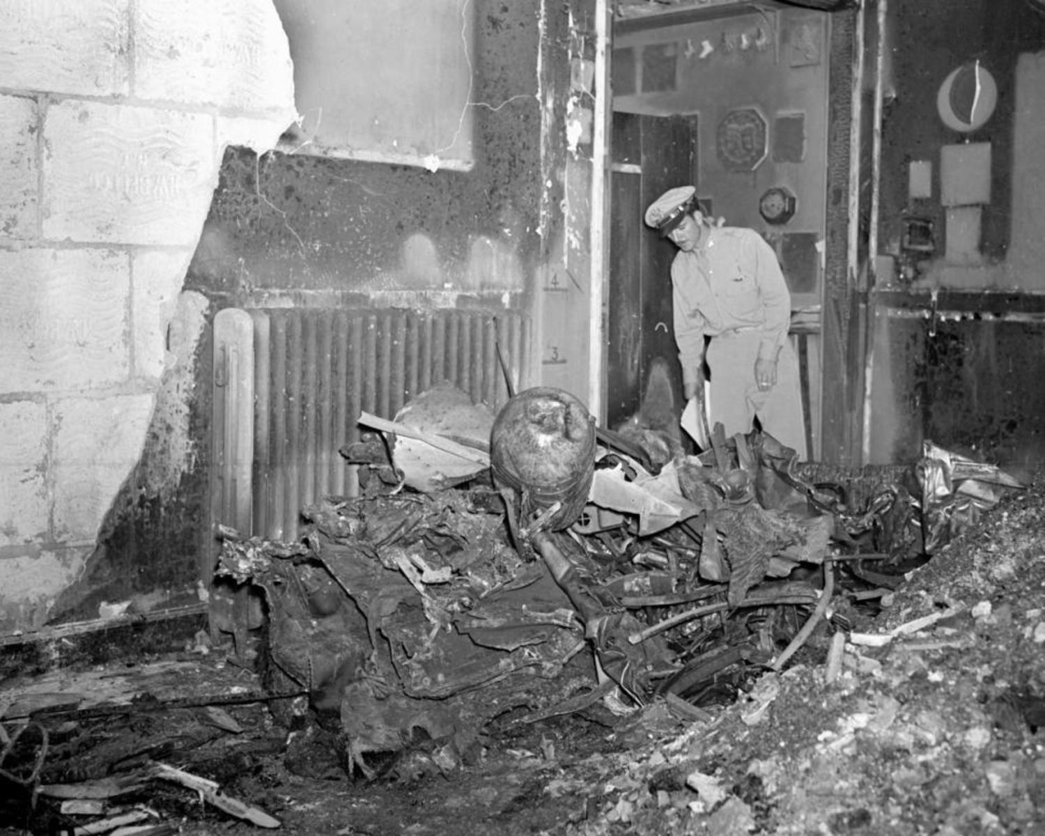 One of the bomber's motors, trailing part of the plane, crashed through two walls of the building, plummeted through roof and ended up burning in studio at 10 W. 33d St.