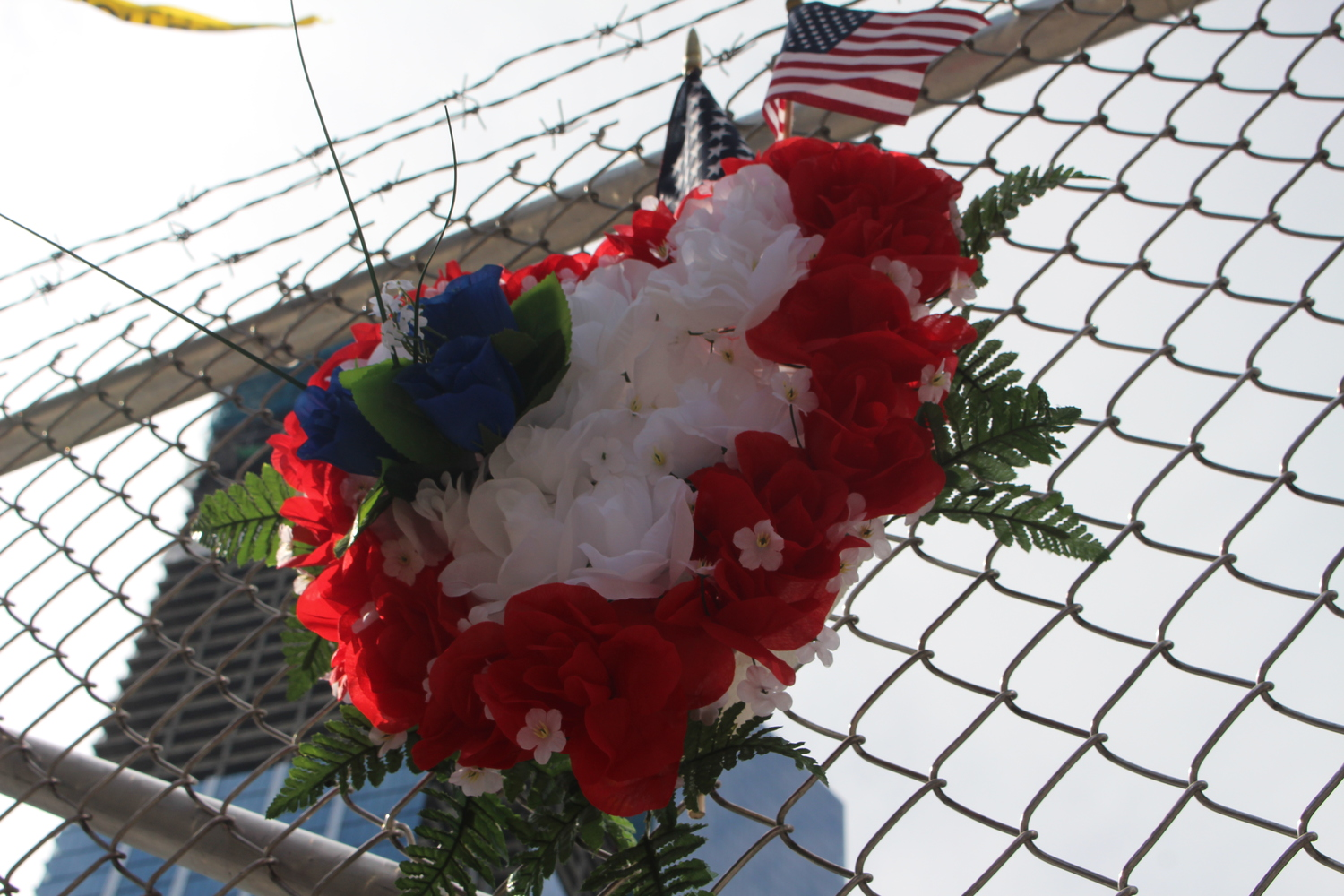 detail shot | An American flag and order of flowers hung on a fence outside of the World Trade Center Site. Photo by Brelaun Douglas.