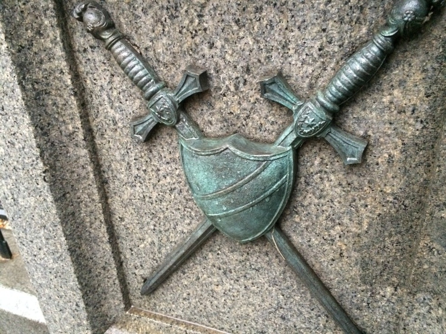 One of the bronze relief images, crossed swords and shield