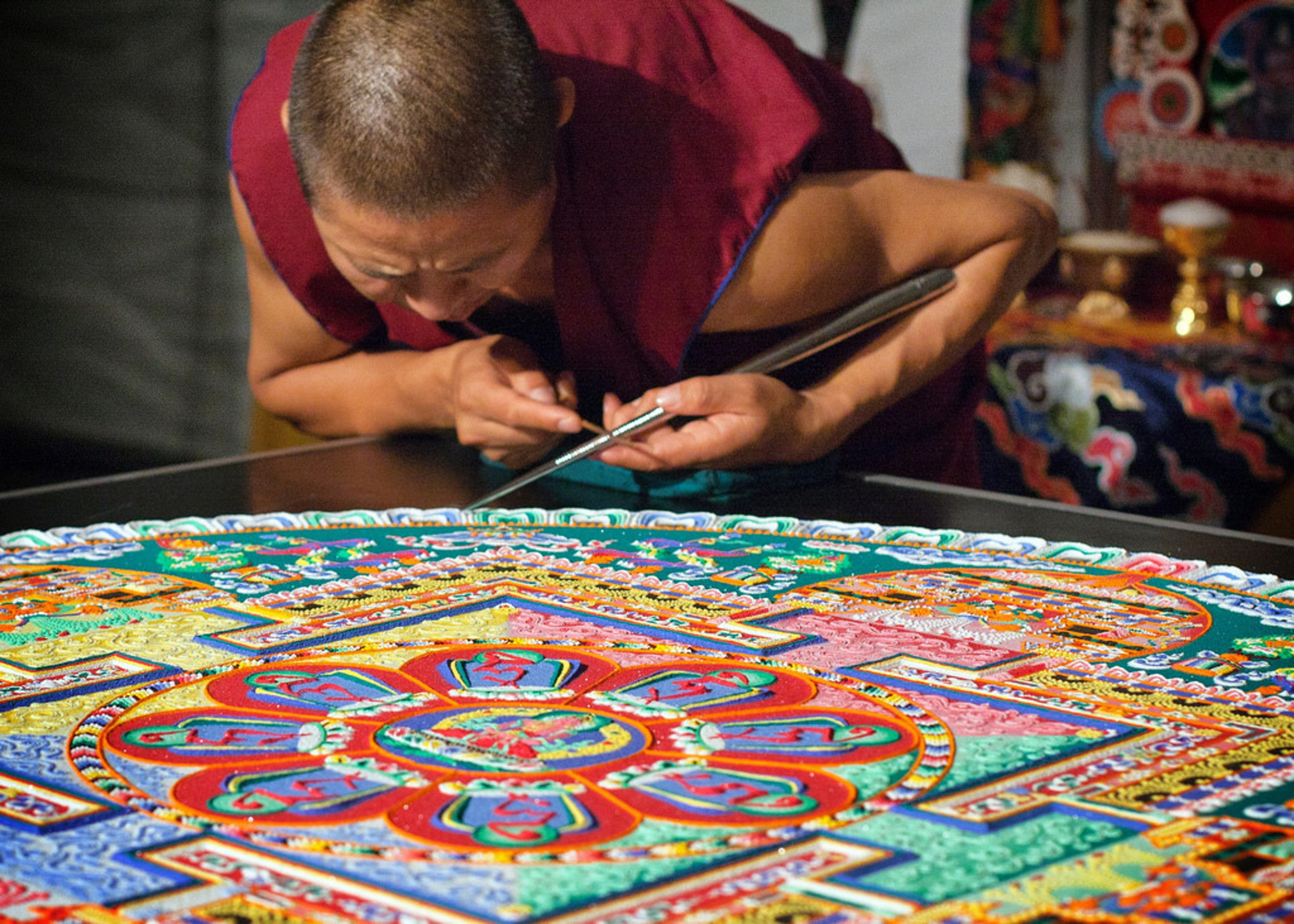 Tibetan monk adding sand to a mandala