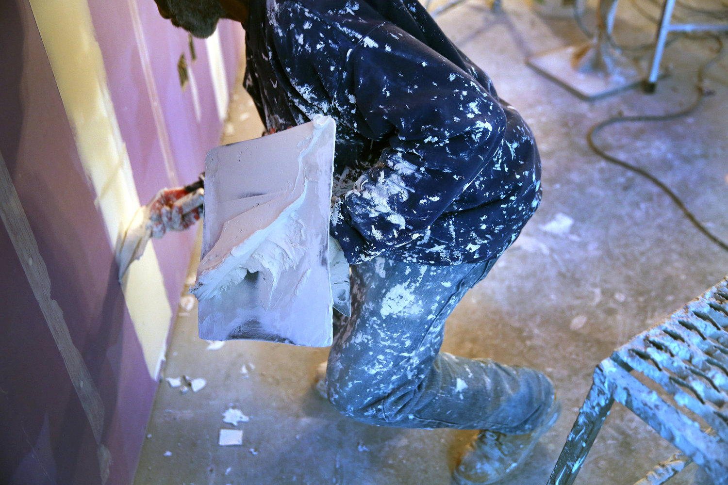 A worker applies joint compound to drywall.