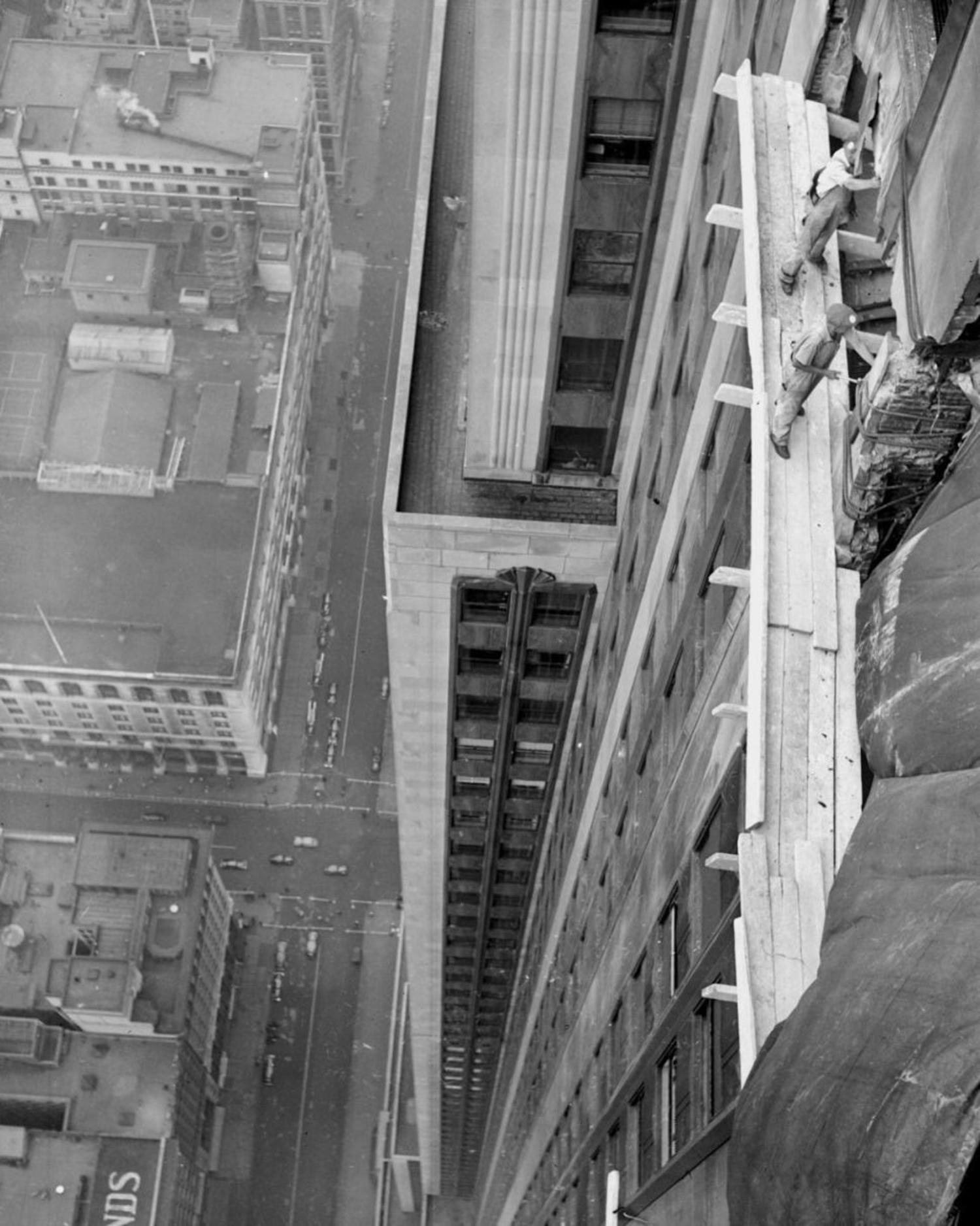 Workmen begin the costly job of repairing the damage done to the worl'd highest building the freak plane crash.