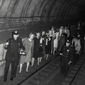 Police officers lead commuters through a subway tunnel where they were trapped during a power failure on Nov. 20, 1965.