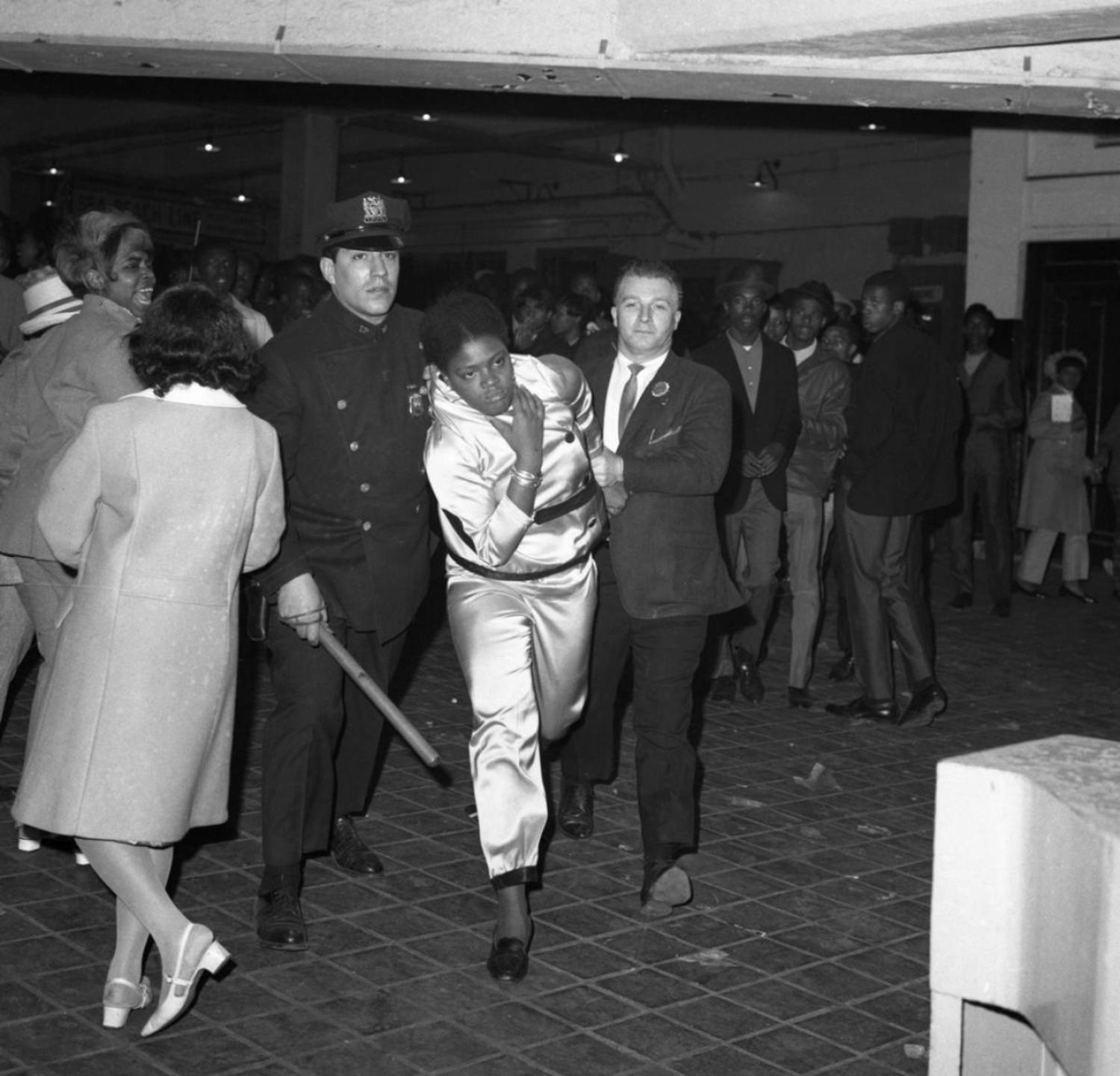 1960's: Police officers escort a member of a mob of disorderly youths away from the subway station at Stillwell Avenue in Coney Island.