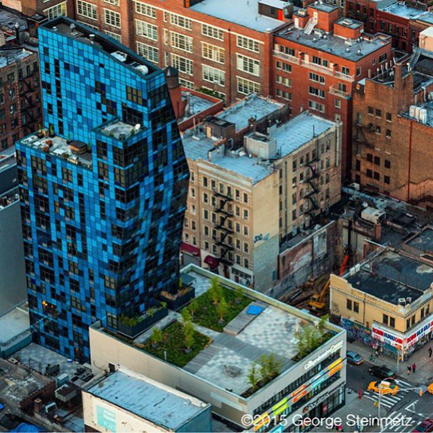 Photograph by George Steinmetz @geosteinmetz / @thephotosociety  Bernard Tschumi's innovative 2007 BLUE residential tower on Manhattan's Lower East Side uses angled walls and roof to allow for maximum floor space on the upper floors. BLUE introduced a new element to a neighborhood whose every-day character is expressed by the storefronts along Delancey Street.